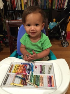 one-year-old sits in a high chair holding oil pastels