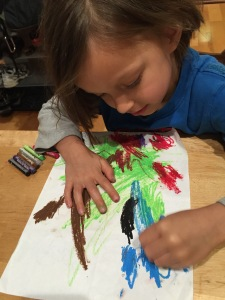 preschool-aged boy colors with oil pastels